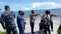 Kapolres Tapteng AKBP Nicolas Dedy Arifianto Membagikan Masker kepada Pengunjung Pantai.