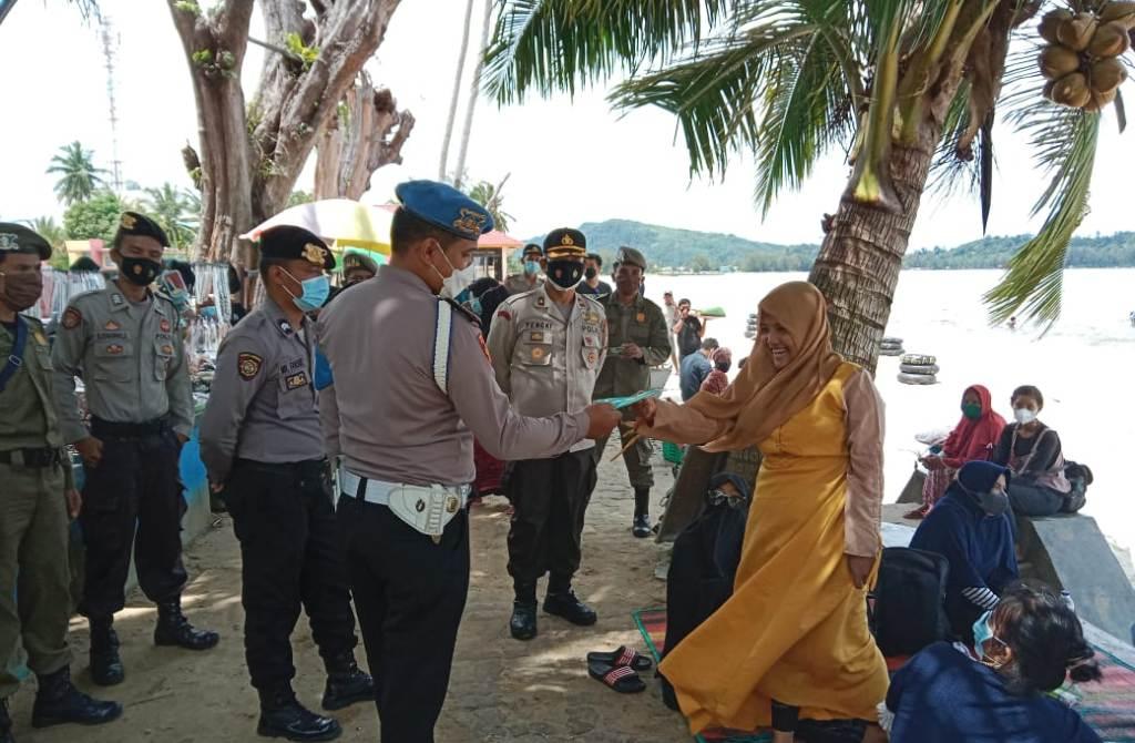 Polisi Menyerahkan Masker kepada Pengunjung Pantai di Tapteng. (dok/istimewa)